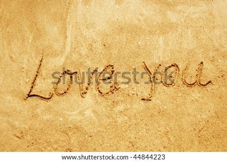 love you handwritten in sand on a beach