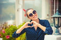 Love you. Portrait close up happy smiling young woman showing heart sign gesture with hands isolated restaurant coffee shop background. Positive human emotion expression feeling attitude body language