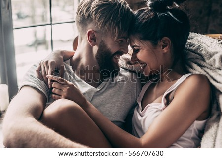 Love you so much! Beautiful young couple smiling and sitting face to face in chair while spending time at home together #566707630