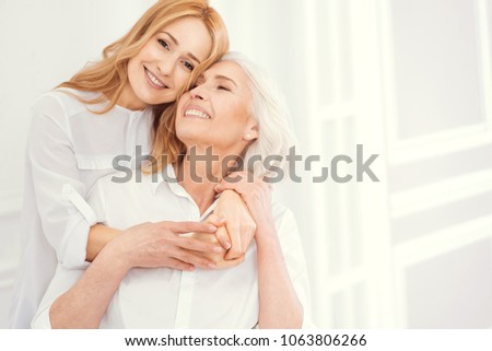 Love you to the moon and back. Full of love charming blonde lady smiling into the camera while standing next to her beautiful mother and hugging her tightly to express her love.