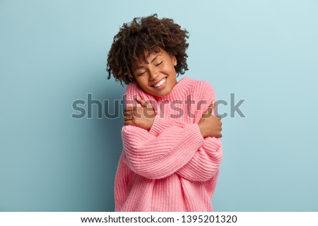 Love yourself concept. Photo of lovely smiling woman embraces herself, has high self esteem, closes eyes from enjoyment, likes her new comfortable soft pink sweater, tilts head, stands indoor