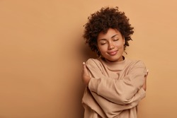 Love yourself, self acceptance. Gentle lovely Afro American woman crosses hands and embraces own body, tilts head and closes eyes, wears comforable brown sweater, models indoor. I love myself