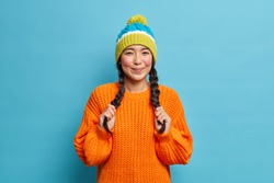 Lovely adorable ethnic girl keeps hands on pigtails being in happy mood wears knitted hat and orange sweater poses over blue background. Youth fashion emotions lifestyle concept. Fashionable teenager