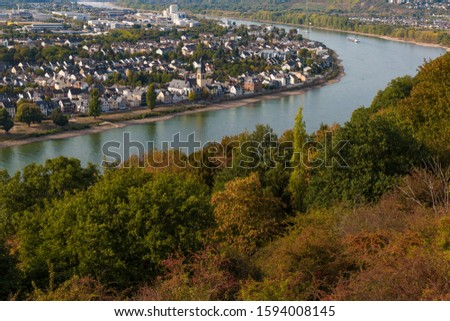 Lovely aerial view of the Rhine river, the city Koblenz at the riverbank and the colourful trees along the hill viewed from the wooden viewing platform near the Ehrenbreitstein Fortress on a nice day.
