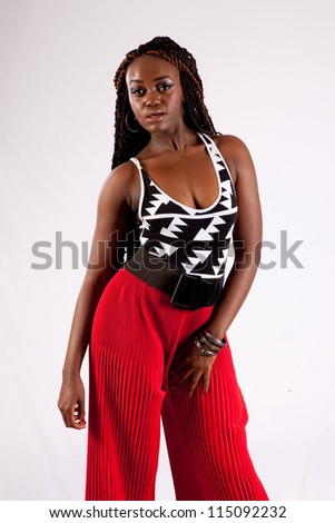 Lovely African American black woman in red slacks, looking at the camera with a friendly but serious expression with her hands on her thighs