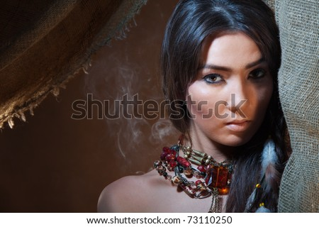 Lovely and passionate look from a tent of American Indian girl - studio photo with professional makeup