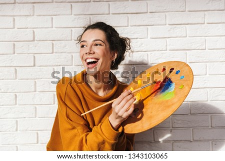 Lovely artistic woman holding color palette for painting indoors over white wall