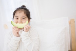 Lovely Asian child girl eating delicious green melon