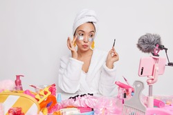 Lovely Asian female mdel holds professional brush puts undereye patches uses tools for makeup records video blog for social network sites gives beauty and skin care advice wears bathrobe towel on head