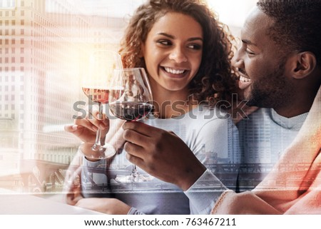 Lovely atmosphere. Close up of joyful young couple drinking wine while looking at each other and showing true emotions