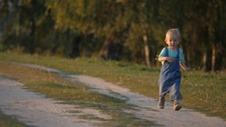 Lovely baby child running on dusty countryside road, kid enjoying life, slow motion