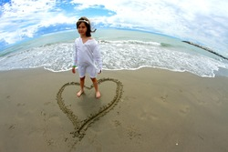 lovely baby girl inside a heart on the beach by the sea