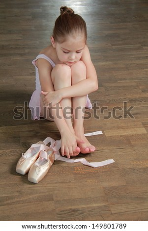 Lovely ballerina puts on pointe in ballet class at the old wooden dance floor