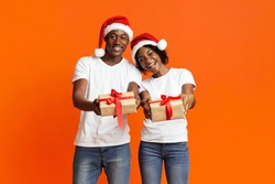 Lovely black couple showing their Christmas gift over orange studio background, copy space. Happy african american family wearing Santa hats and celebrating New Year 2021 together, holding present