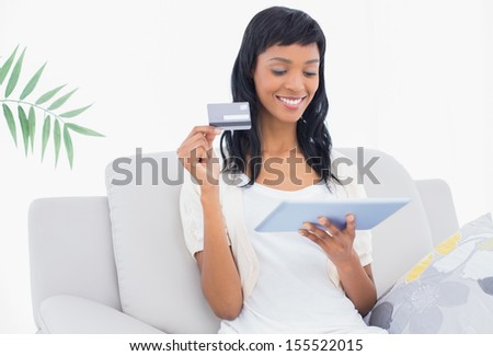 Lovely black haired woman buying online with her tablet pc in a living room