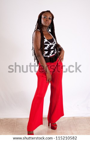 Lovely black woman in red slacks, standing with her hands on her hips and looking at the camera with a thoughtful expression