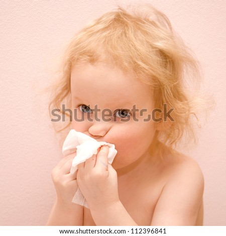 Lovely blond curly-haired baby girl with blue eyes is sick. She has a runny nose. Blowing her nose with disposable tissues. Isolated on pink background - stock photo