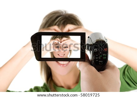 Lovely blond girl with hands as heart at camcorder