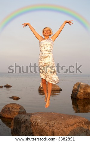 lovely blond jumping at the seashore under colorful rainbow