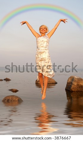 lovely blond jumping in water under colorful rainbow