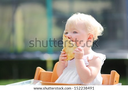 Lovely blond little baby girl in beautiful white dress biting on piece of tasty pizza holding it with two hands