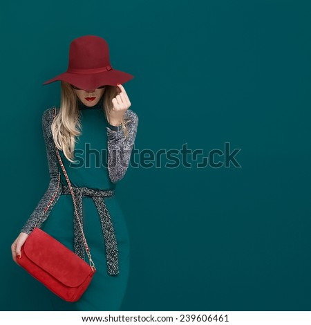 Lovely Blond model in fashionable red Hat and a red Clutch on green background