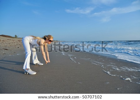lovely blonde female model stretches on florida beach in morning