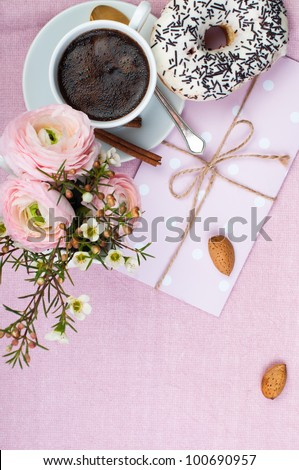 Lovely breakfast in pink colors with coffee, flowers and sweets.