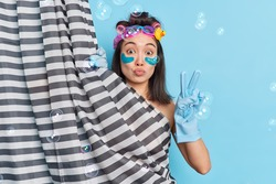 Lovely brunette Asian woman applies collagen patches while taking douche makes peace gesture undergoes beauty procedures hides behind shower curtain poses against blue background soap bubbles around