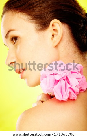 Lovely brunette with pink flower over yellow background