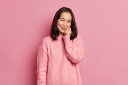 Lovely brunette woman with eastern appearance keeps hand on face has gentle smile looks satisfied at camera has dimples on rouge cheeks poses against pink background. Cute glad Asian girl indoor