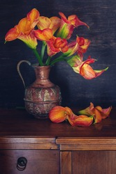 Lovely bunch of flowers . Beautiful bouquet off orange calla flowers in a antique copper vase on the table.