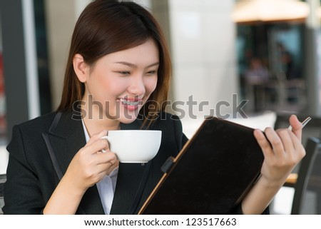 Lovely business woman reading notes in her organizer