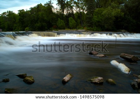 Lovely calm looking water with a time exposure of the Milwaukee River Waterfall in summer.  A beautiful calming scenic at Kletzsch Park.