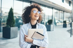 Lovely caucasian businessperson with curly hair posing outside with a tablet and laptop while wearing eyeglasses in a sunny day