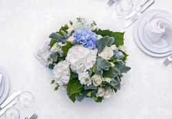 Lovely centered wedding or social event table decoration with wine glass, cutlery and napkins. Copy space.