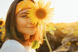 Lovely cheerful young woman posing alone on camera. Cover part of face with yellow sunflower blossom. Femlae model posing alone in middle of sunflower field. Morning or evening. Summertime