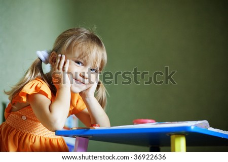 Lovely child sitting at table looking at camera and smiles