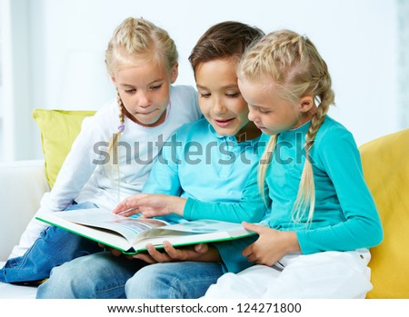 Lovely children looking through a picture book