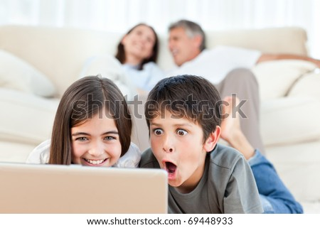 Lovely children watching a movie on their laptop at home