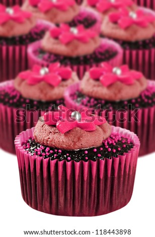 Lovely chocolate cupcakes in pink cups - very shallow depth of field - stock photo