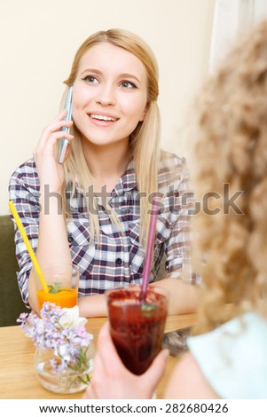 Stock Photo Lovely conversation. Beautiful smiling girl in cafe talking per mobile phone and looking aside.