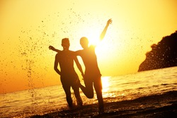 Lovely couple at the beach runs to sunset. Tropical sea travel