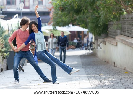 Lovely couple dancing West Coast Swing in the streets, carefree and happy. #1074897005