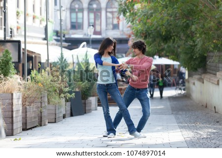 Lovely couple dancing West Coast Swing in the streets, carefree and happy. #1074897014