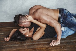 Lovely couple fitness boy and girl hugging on the floor and kiss each other