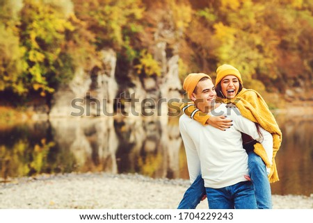 Lovely couple having fun together in nature. Fashion couple enjoying autumn. Boyfriend carrying his girlfriend on piggyback.Young couple walking near lake in autumn.Fashion, lifestyle and autmn mood. Stockfoto ©