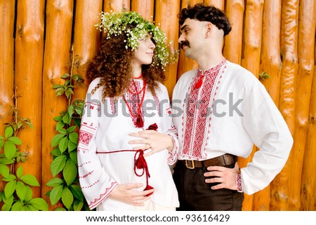 ... in Ukrainian national costumes talking outdoors. The woman is pregnant