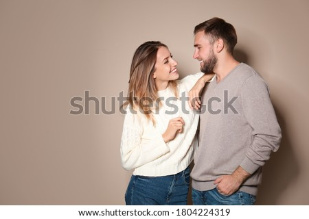 Lovely couple in warm sweaters on beige background