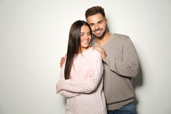 Lovely couple in warm sweaters on light background